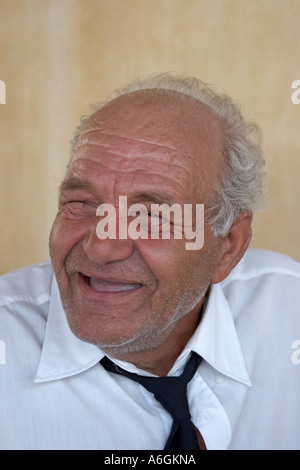 Local old man with black tie smiling in town of Pyrgos or Pirgos on Greek Island of Santorini or Thira Greece - Stock Photo