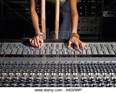 Woman using mixing desk - Stock Photo