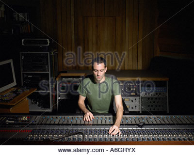 Music producer using mixing desk - Stock Photo