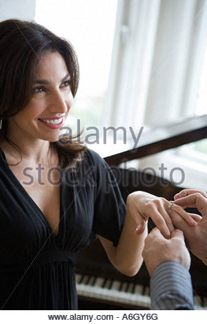 Man putting engagement ring on womans finger - Stock Photo