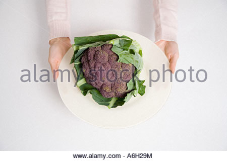 Person holding a plate of purple cauliflower - Stock Photo