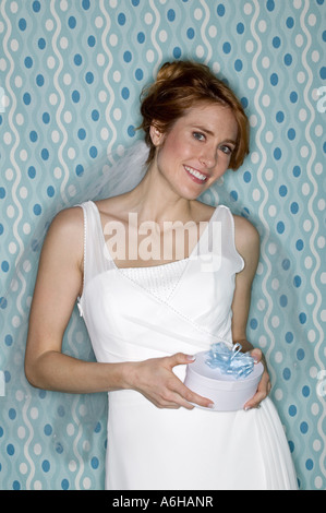 Young bride with red hair holding gift wedding day studio blue background - Stock Photo