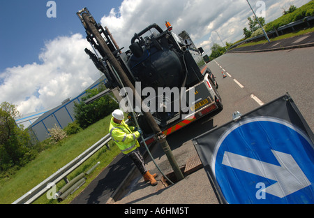 Roadworks for drain clearance on a road in England - Stock Photo