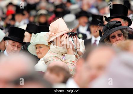 Woman at Royal Ascot horse race, looking through binoculars, York, Great Britain - Stock Photo