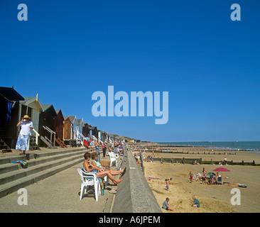 Frinton beach huts behind the promenade along the wide sandy beach looking East towards Walton - Stock Photo