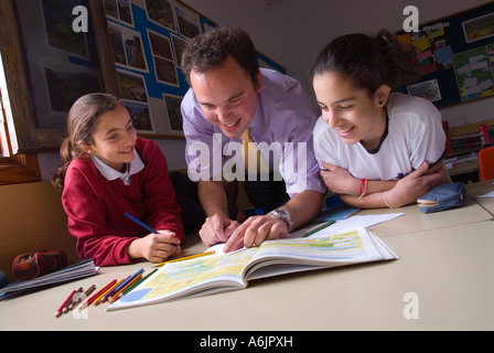 Teacher and junior pupils in school classroom happily interacting together on a geography mapping project - Stock Photo