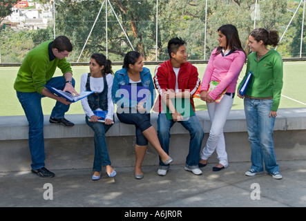 School Group of six senior teenagers meet up and talk in sunny school playground campus - Stock Photo