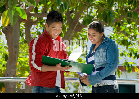 Two smiling senior teenage students compare study notes outside in school garden playground campus - Stock Photo