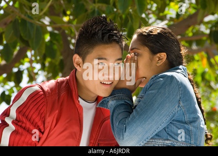 SCHOOL PLAYGROUND SECRETS WHISPERS Teenage school girl whispers secret to listening teenage boy outside in a sunny - Stock Photo