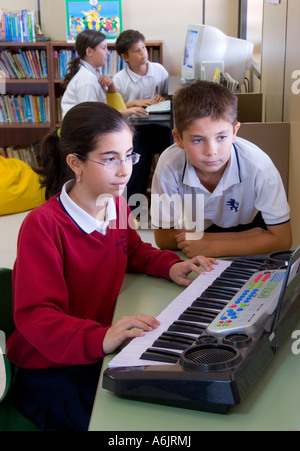 Junior school pupils in free study period catching up on their music and computer studies in school library - Stock Photo