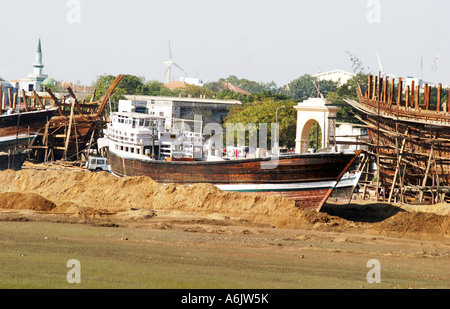 windpower flanks Dhow building at Mandavi Port in Gujarat India - Stock Photo