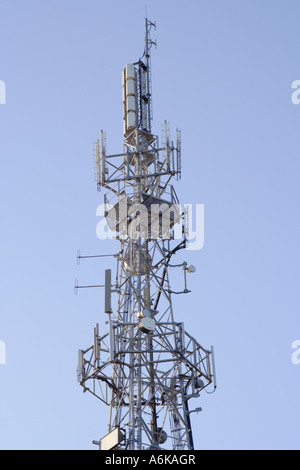 top of communication mast against a blue sky - Stock Photo