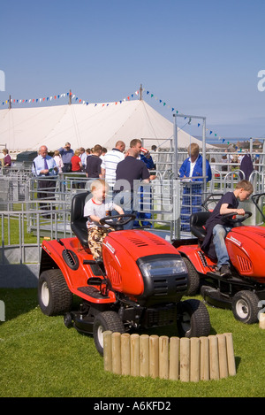 dh County Show KIRKWALL ORKNEY Children trying out Lawnflite lawnmower machines at show ground display - Stock Photo