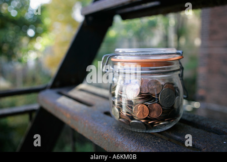 Jar filled with coins on fire steps close up - Stock Photo