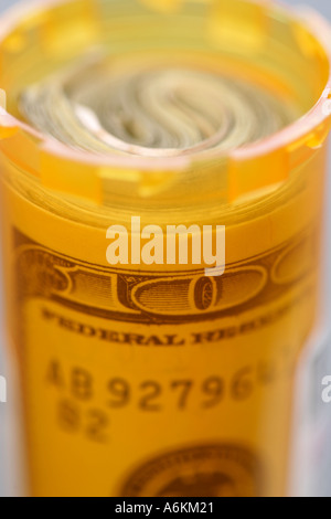 Pill bottle with 100 dollar bill inside close up - Stock Photo
