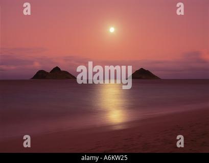 Full Moon rising at Lanikai Beach Oahu Hawaii The moon is rising between the twin Mokulua Islands - Stock Photo