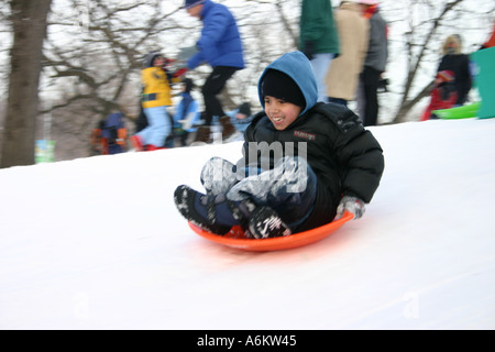 Hispanic boy aged 7 or 8 years old sledding in Lincoln Park Chicago IL USA - Stock Photo
