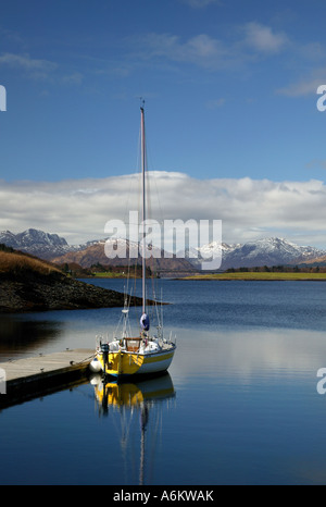 Lone yacht reflected in Loch Leven, Ballachulish, Lochaber, Scotland, with snowcapped Corbetts of Ardgour in the - Stock Photo