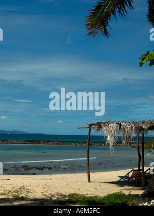 Empty beach, two deck chairs under palm leaf canopy on Koh Larn aka Coral Island, Pattaya, Thailand - Stock Photo