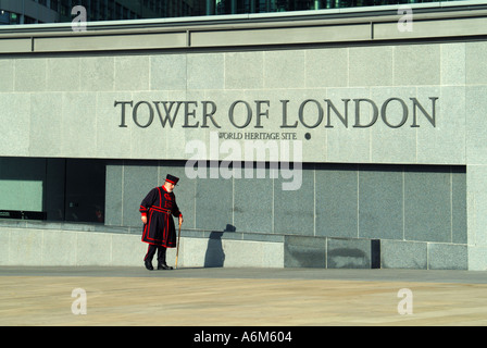 Tower Hill remodelled approach areas to the Tower of London with yeoman warder walking past new sign panel - Stock Photo