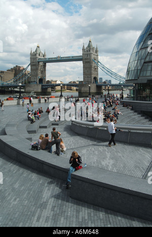 Paved riverside walkways between Greater London Authority City Hall offices and River Thames with Tower Bridge - Stock Photo