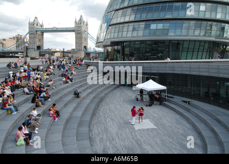 Riverside walkways between Greater London Authority City Hall offices & River Thames with dancing music event in - Stock Photo
