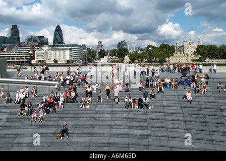 Riverside walkways between Greater London Authority City Hall offices River Thames with City skyline people relaxing - Stock Photo