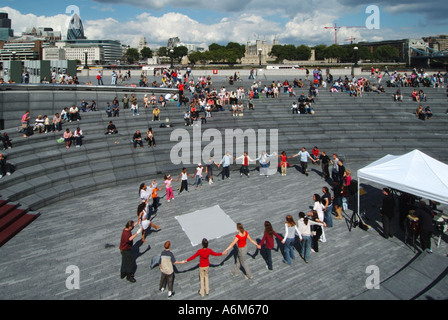 Riverside walkways between Greater London Authority City Hall offices River Thames with dancing music event - Stock Photo