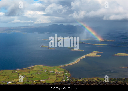A dramatic view of Clew Bay with a rainbow from the top of Croagh Patrick - Stock Photo