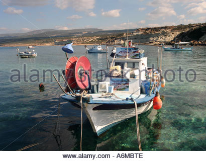 A fishing boat waits in the harbour at Agios Georgios, Western Cyprus, on a bright Winters day. - Stock Photo