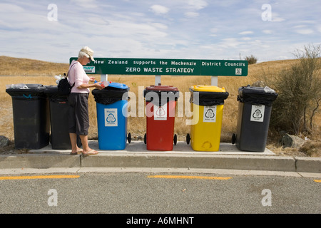 Tourist placing plastic bottle in colourful recycling bins at visitor centre near Lake Pukaki Mackenzie District - Stock Photo