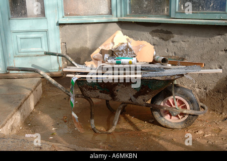 A BUILDERS WHEELBARROW FULL OF RUBBISH OUTSIDE OF A HOUSE UNDER RENOVATION UK - Stock Photo