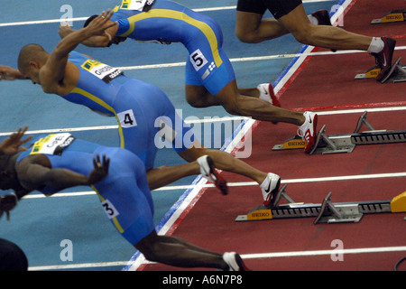 mens 60 meter sprinters explode from the starting blocks in an indoor competition - Stock Photo