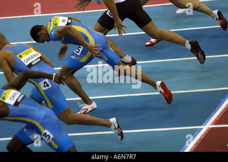 Male runners explode from the starting blocks in a indoor sprint competition - Stock Photo