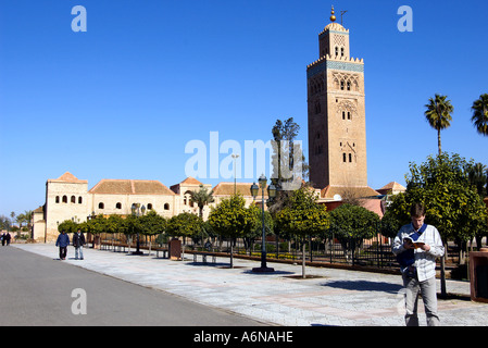 a male English tourist is looking up a tour guide book in front of the Koutoubia Koutoubia Minaret in Marrakesh - Stock Photo