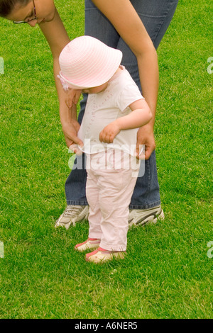 Mother helping toddler - Stock Photo