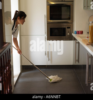 Young woman mopping kitchen floor, side view - Stock Photo