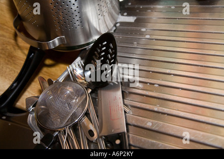 Selection of stainless steel cutlery and kitchen utensisl on sink draining board after washing up. Free space for - Stock Photo