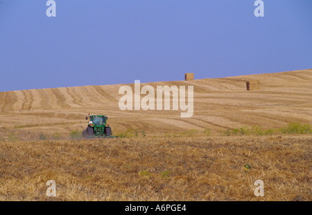 tractor driving through harvested wheat field Andalusia Spain - Stock Photo