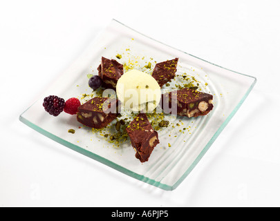 CHOCOLATE BROWNIE PIECES WITH ICE CREAM AND PISTACHIO AND FRUIT GARNISH - Stock Photo
