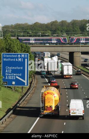 M25 motorway busy but moving traffic fast train on bridge - Stock Photo