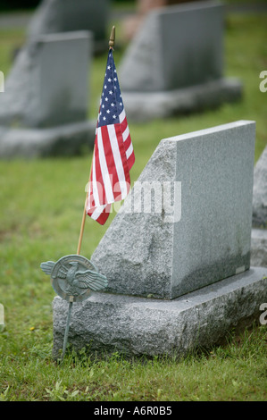 The flag of the United States of America rest next to a head stone of a grave of a veteran of the armed forces in - Stock Photo