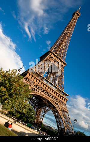 Eiffel Tower couple sitting on ground in foreground Paris France Europe - Stock Photo