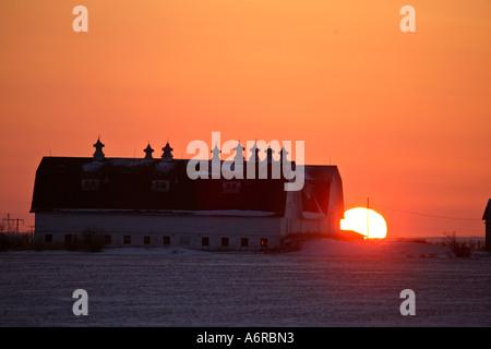 Sun setting behind a large barn in scenic Saskatchewan Canada - Stock Photo