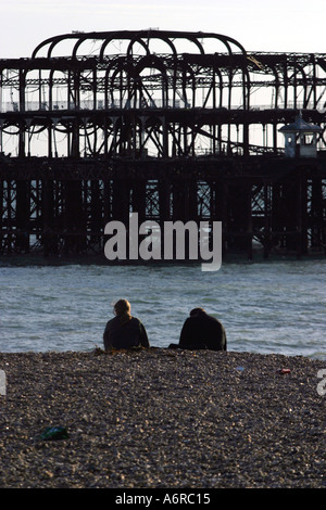 A couple sit on the beach in front of the ruins of Brighton West Pier East Sussex England which was destroyed by fire in 2003 Stock Photo
