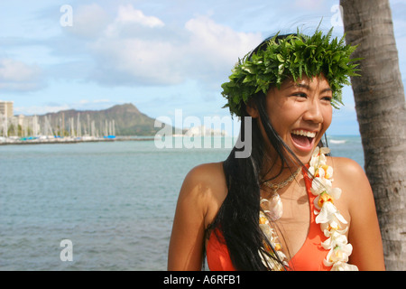 Young Hawaiian woman with lei smiles with Diamond head crater in backround honolulu waikiki oahu hawaii - Stock Photo