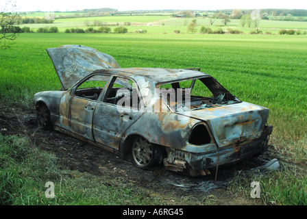 Essex burnt out car left in farmers field who then has the responsibility to dispose of it - Stock Photo