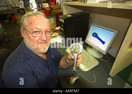 mature worker with CAD computer aided design piston cam shaft in metal workshop - Stock Photo