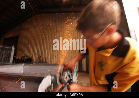 young worker with angle grinder - Stock Photo