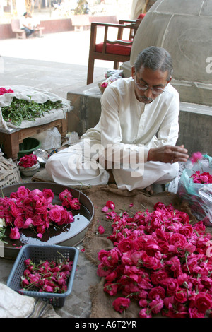 Man selling flower offerings at the entrance to the  Hathee Singh Temple Ahmedabad Gujarat India - Stock Photo